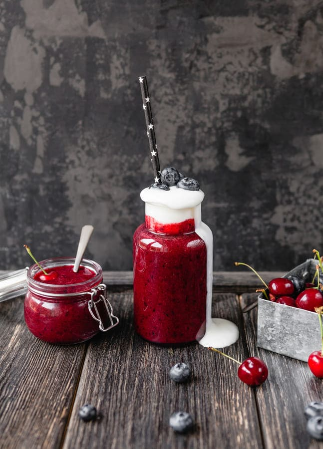 Fresh healthy compote on rustic table with cherries and straws